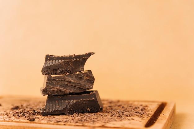 Pedaços de chocolate e pedaços de chocolate na tábua de cortar Foto gratuita