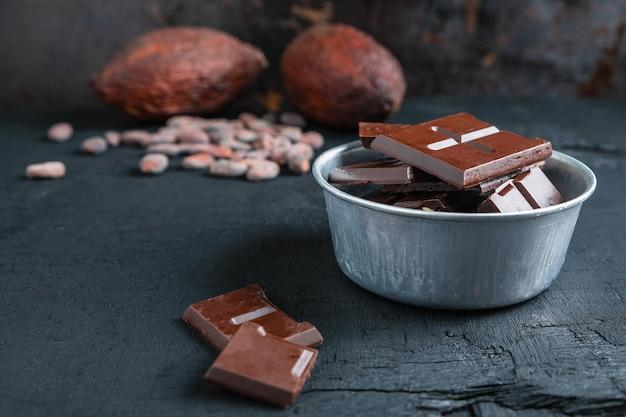 Pedaços de chocolate escuro e grãos de cacau na mesa Foto Premium