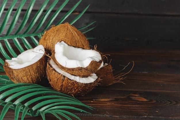 Pedaços de coco rachado no escuro de madeira Foto Premium