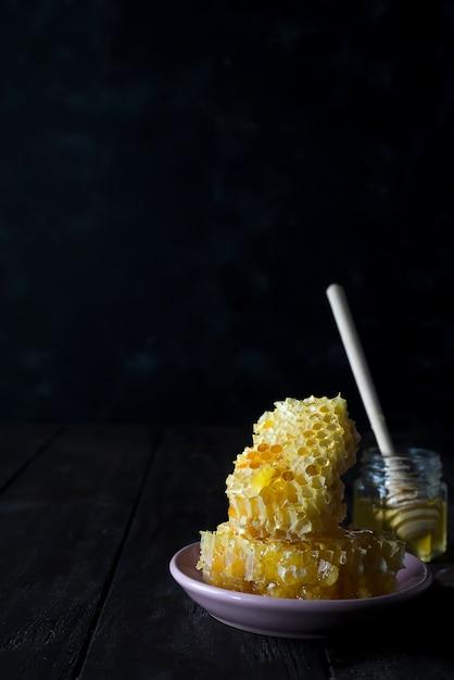 Pedaços de favo de mel fresco com uma concha de madeira pingando mel em uma placa de cerâmica Foto Premium