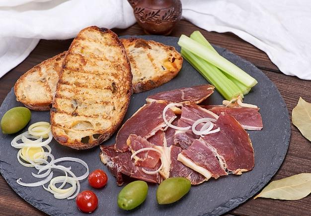 Pedaços de jamon e pão frito branco para um sanduíche Foto Premium