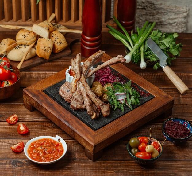 Pedaços de kebab de costelas de cordeiro servidos com batatas, ervas e salada de rabanete Foto gratuita