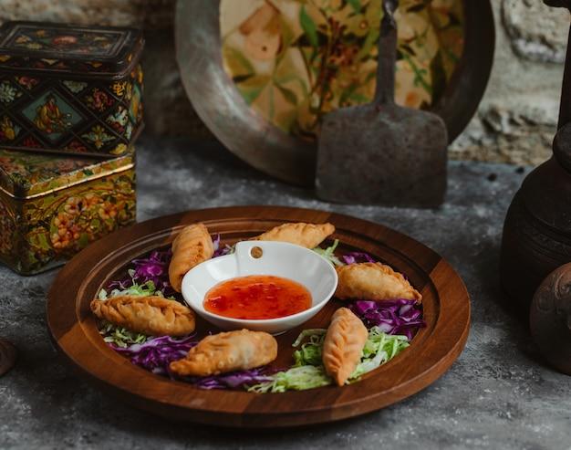 Pedaços de khingal assados servidos com molho de pimenta quente. Foto gratuita