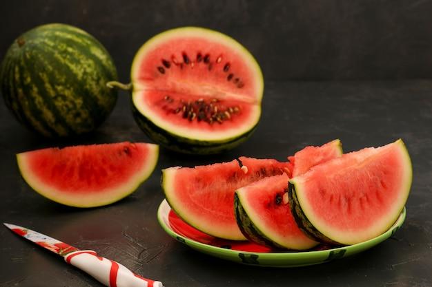 Pedaços de melancia suculenta estão localizados em um prato sobre um fundo escuro Foto Premium