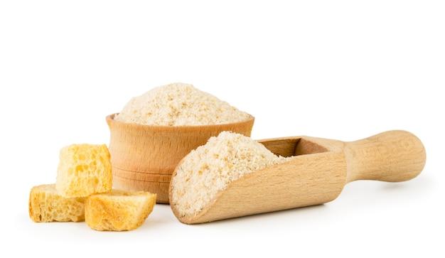 Pedaços de pão seco e pão ralado em uma tigela de madeira e colher Foto Premium