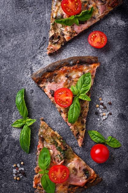 Pedaços de pizza preta com tomate e manjericão Foto Premium