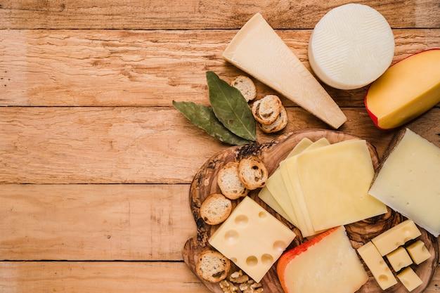 Pedaços de queijo diversos; folhas de louro e fatias de pão na mesa de madeira Foto gratuita