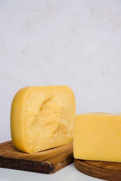 Pedaços de queijo gouda na tábua de madeira contra o pano de fundo texturizado em mármore Foto gratuita