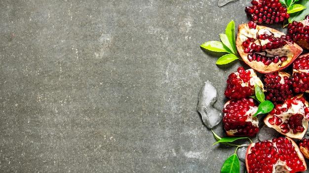 Pedaços de romã madura com folhas e gelo. na mesa de pedra. espaço livre para texto. vista do topo Foto Premium