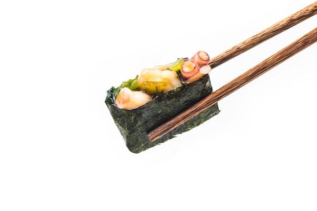 Pedaços de sushi colocados entre pauzinhos Foto Premium