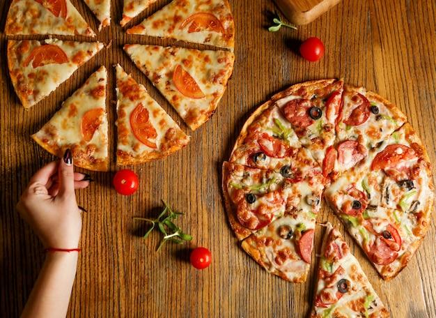 Pedaços fatiados de pizza mista com linguiça e pizza com queijo e tomate Foto gratuita