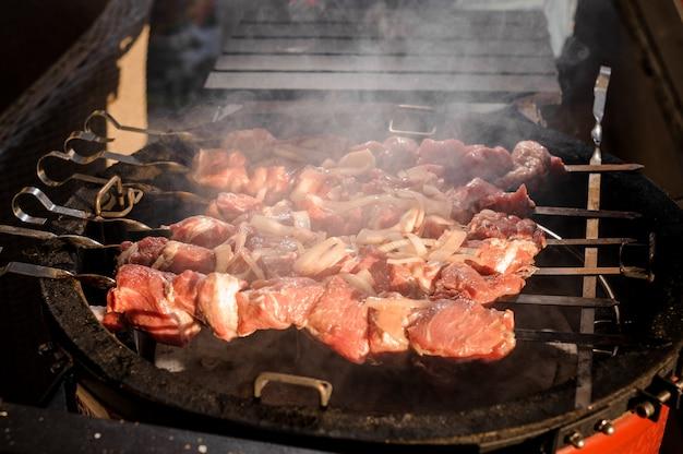 Pedaços grandes de carne no espeto deitado na grelha Foto Premium
