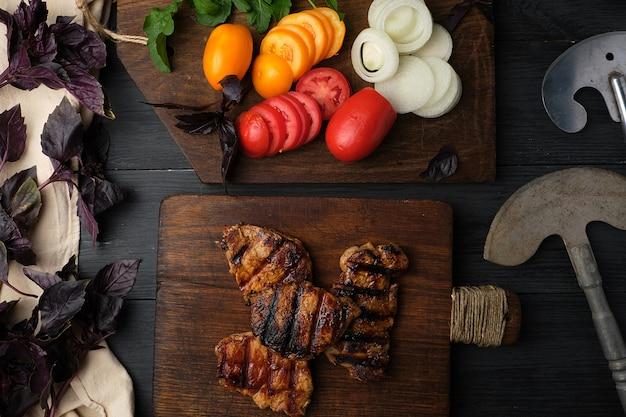 Pedaços grelhados de carne de porco, ao lado de uma tábua com legumes frescos picados Foto Premium
