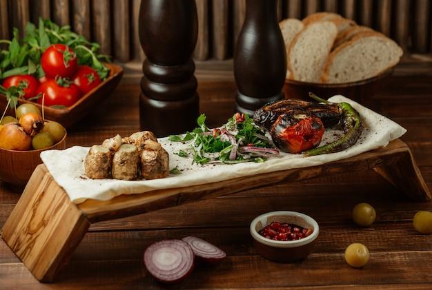 Pedaços pequenos de carne assada com salada verde em um pedaço de lavash, yukha Foto gratuita