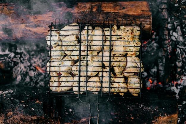Pedaços quentes de frango defumado em brasas e lenha queimada. Foto Premium