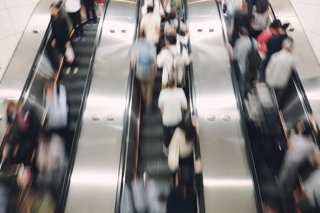 Pedestre, assalariado subindo e descendo a escada rolante automática Foto Premium