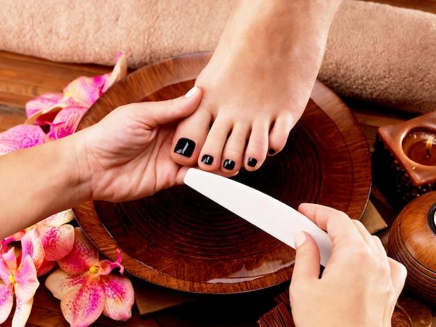 Pedicure mestre faz pedicure nas pernas da mulher - conceito de tratamento de spa Foto gratuita