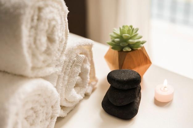 Pedra negra quente; vela acesa; planta de cacto e enrolado em toalha branca Foto gratuita