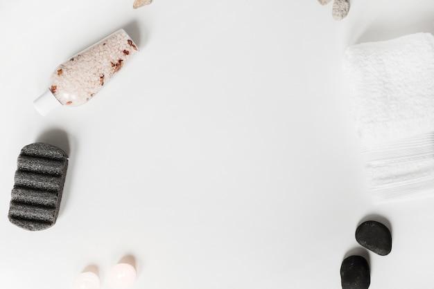 Pedra pomes; sal de ervas; pedra de spa; velas e toalha no fundo branco Foto gratuita