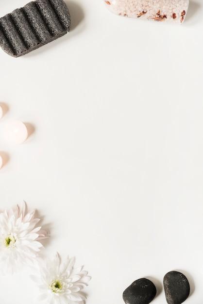 Pedra pomes; sal; último; velas e flores sobre fundo branco Foto gratuita