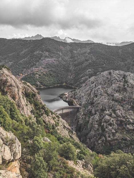 Pedras altas, cobertas de vegetação e vista para um lago sob um céu nublado Foto gratuita