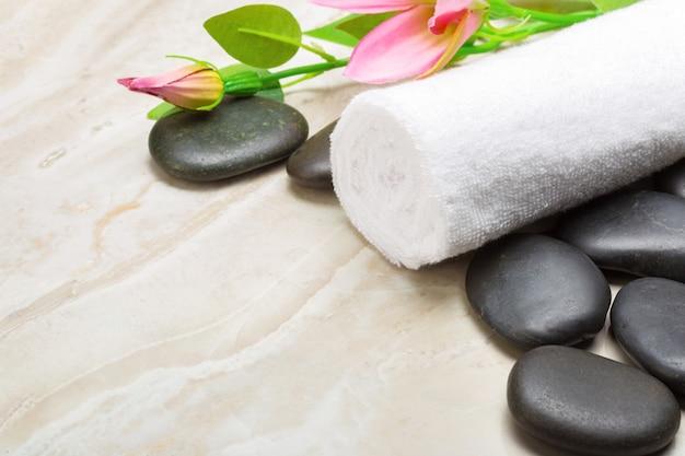 Pedras de spa, toalha e flores sobre fundo de madeira Foto Premium