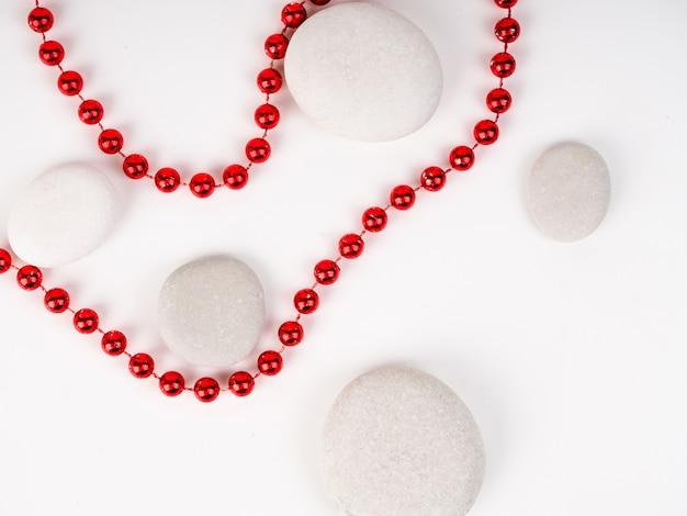 Pedras do mar branco e contas vermelhas entre eles. belas contas brilhantes vermelhas Foto Premium