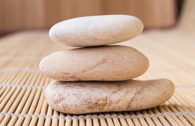 Pedras empilhadas em uma pirâmide para meditação, esteira de bambu de fundo Foto Premium