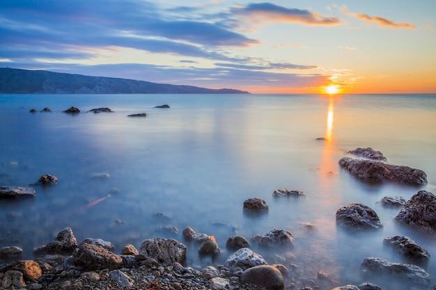 Pedras no oceano contra o pôr do sol, sobre o qual a névoa Foto Premium