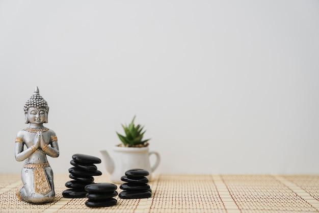 Pedras vulcânicas, figura buddha e pote de flores Foto gratuita