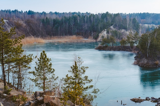 Pedreira bonita perto do lago coberto de gelo fino Foto gratuita