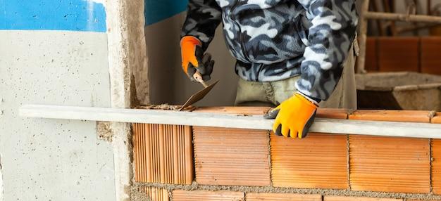 Pedreiro que instala a alvenaria do tijolo na parede interior. Foto Premium