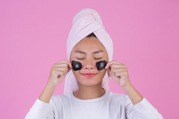 Peeling cosmético de beleza. a fêmea nova com preto retira a máscara no produto cosmético da casca dos cuidados com a pele da pele no rosto em um rosa. Foto gratuita
