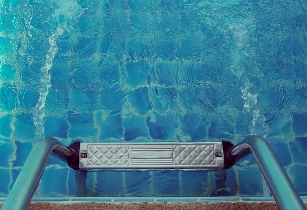 Pegue a escada de barras na piscina azul. Foto Premium