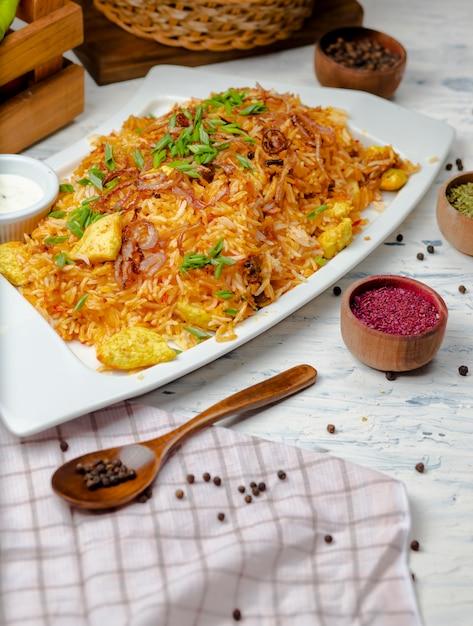 Peito de frango, arroz molho de tomate, risoto, plov com ervas, iogurte e sumakh em chapa branca Foto gratuita
