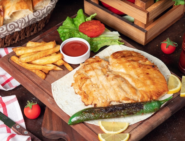 Peito de frango assado com batatas fritas em panela com legumes e ketchup na placa de madeira Foto gratuita