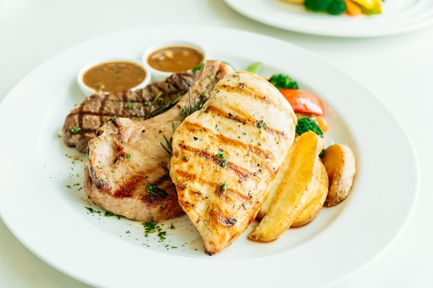 Peito de frango e costeleta de porco com bife de carne e vegetais Foto gratuita