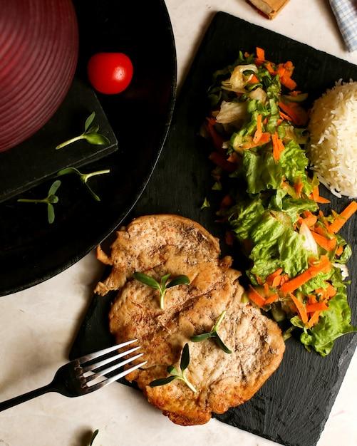 Peito de frango frito servido com salada de alface e arroz Foto gratuita