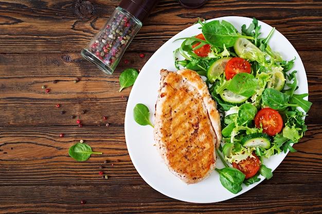 Peito de frango grelhado e salada de legumes frescos - folhas de tomate, pepino e alface. salada de galinha. comida saudável. postura plana. vista do topo Foto gratuita