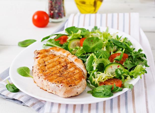 Peito de frango grelhado e salada de legumes frescos - folhas de tomate, pepino e alface. salada de galinha. comida saudável. Foto Premium