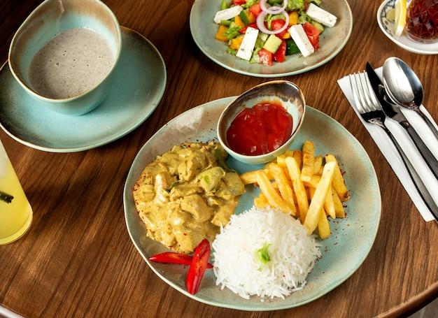 Peito de frango picado, preparado com molho e servido com arroz, batata frita, ketchup, salada e sopa Foto gratuita