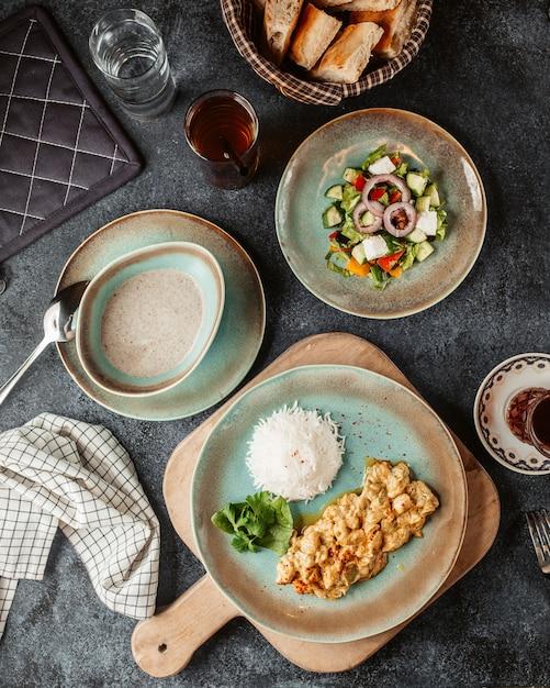 Peito de frango picado, preparado com molho e servido com salada de arroz e sopa Foto gratuita