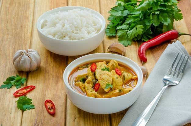 Peito de frango picante em molho de curry amarelo com alho e pimenta com arroz cozido em uma tigela Foto Premium