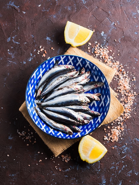 Peixe azul. anchovas em um prato com sal rosa Foto Premium