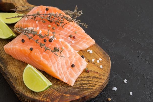 Peixe cru de bife de salmão preparado para cozinhar. vista superior na mesa preta. Foto Premium