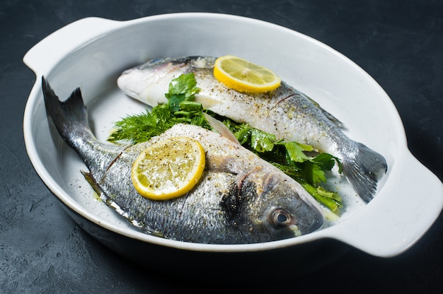 Peixe cru dorado marinado em azeite, sal e pimenta, uma fatia de limão por cima. Foto Premium