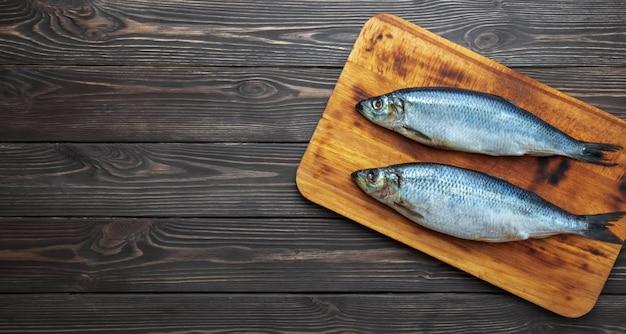 Peixe de arenque atlântico em conserva em uma tábua de corte Foto gratuita