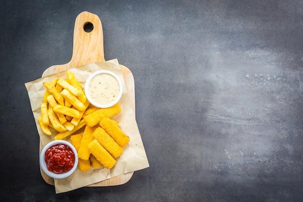 Peixe dedo e batatas fritas ou chips com ketchup de tomate Foto gratuita