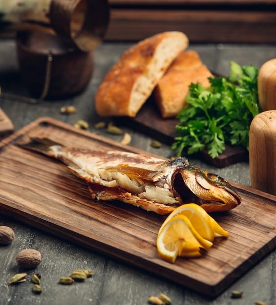 Peixe defumado em uma placa de madeira com uma fatia de limão Foto gratuita