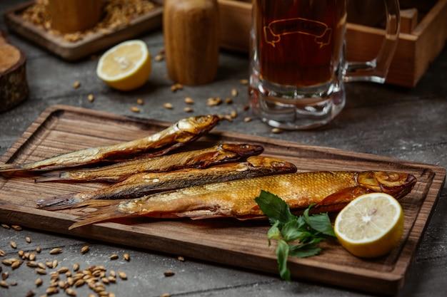 Peixe defumado seco servido com limão na placa de madeira para a noite de cerveja Foto gratuita